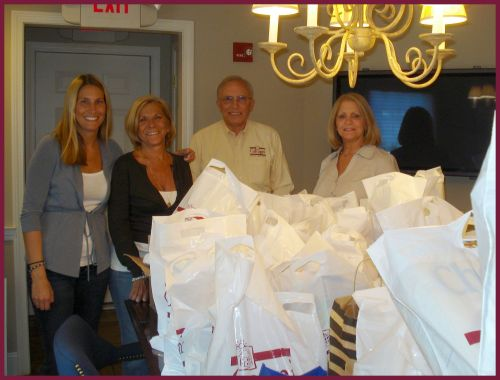 Realtors Lisa Holden, Toni Fazio, Dave Drumheller, and Ellen Gomes, with bags of collected food items