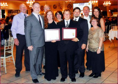 Pictured (Holding awards): Melanie Bristol Ricci, REALTOR; John Ricci, owner of Ricci Construction Group, Inc.